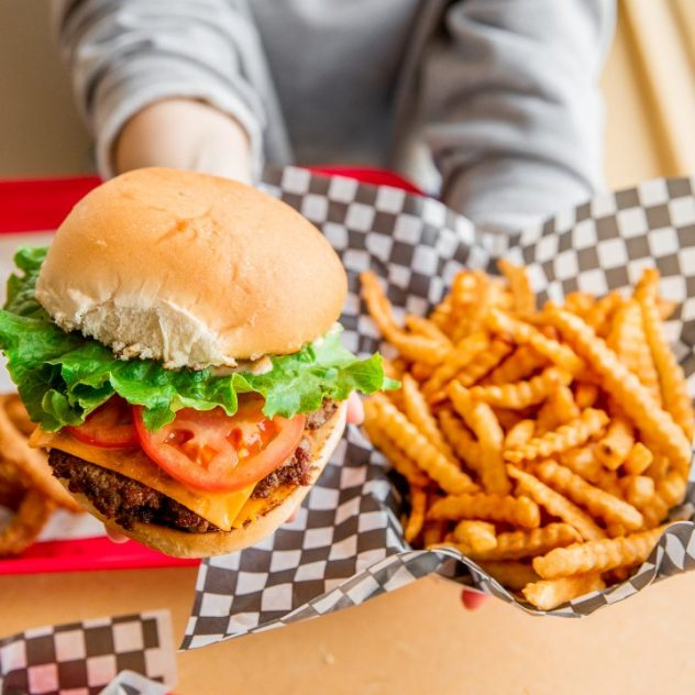 Person holding burger and fries.